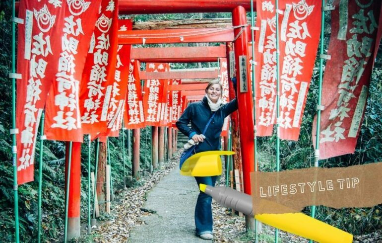 Row of red flags with white Japanese characters, girl standing next to them smiling